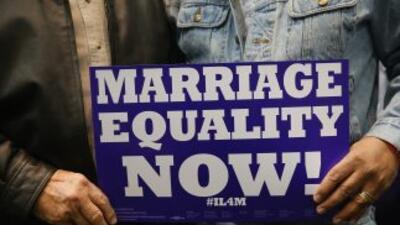 Una pareja sostiene un cartel a favor del matrimonio igualitario.