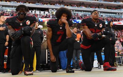 Eli Harold, Colin Kaepernick (centro) y Eric Reid, de los San Francisco...