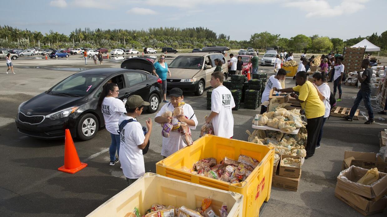 Cada fin de semana, las familias buscan alimentos gratis que aportan las...