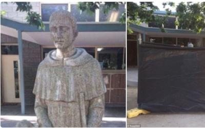 Una estatua de San Martín de Porras que le ofrece un pan a un ni&...