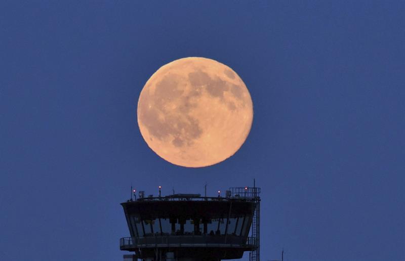 La luna llena, iluminada con un tono ligeramente rojizo, cerca de Schön...