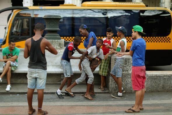 Un grupo de muchachos juegan luchas en el Paseo del Prado,  en el barrio...