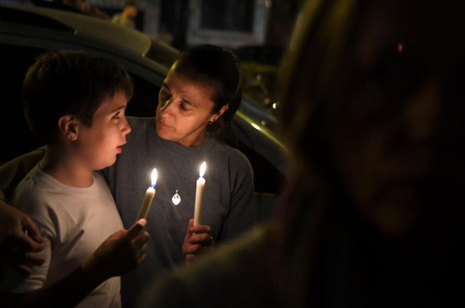 Una mujer y un niño sostienen velas durante una vigilia organizada el mi...