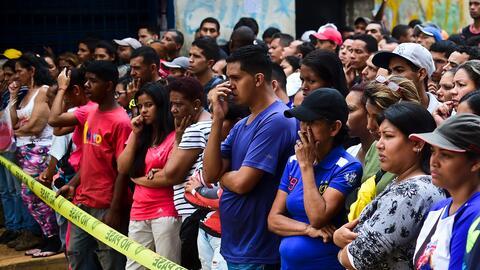 Vecinos observan cómo la policía retira los cuerpos de los...