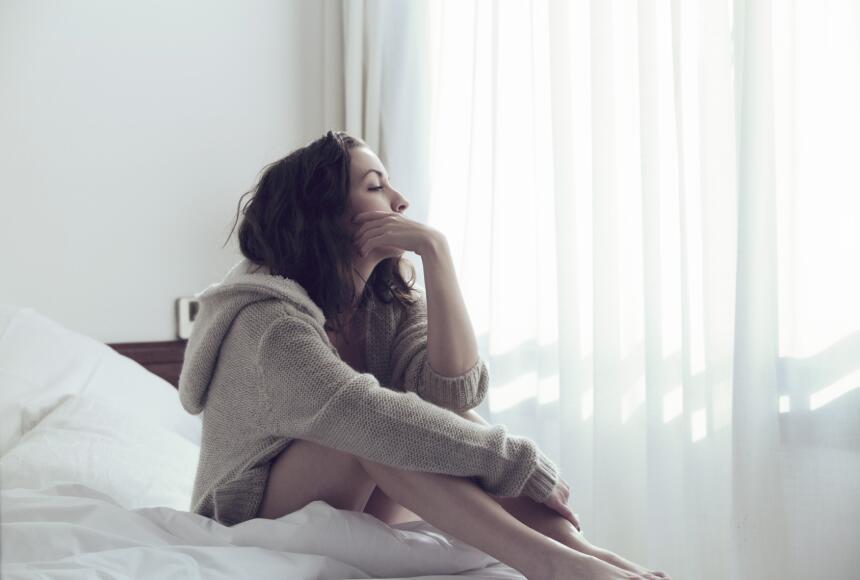 Mujer se encuentra en cama pensativa.