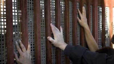 Personas apoyan sus manos contra la valla fronteriza que separa Tijuana...