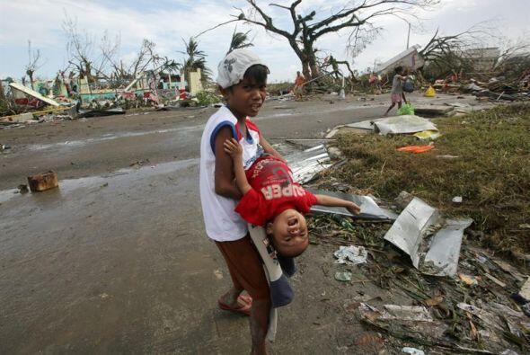 Un niños filipino lleva en brazos a otro pequeño sobreviviente del super...