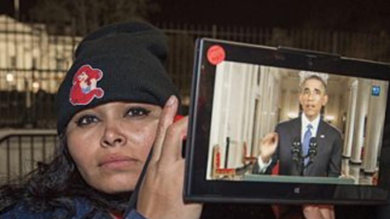 Una inmigrante frente a la Casa Blanca muestra una tabla donde se ve al...
