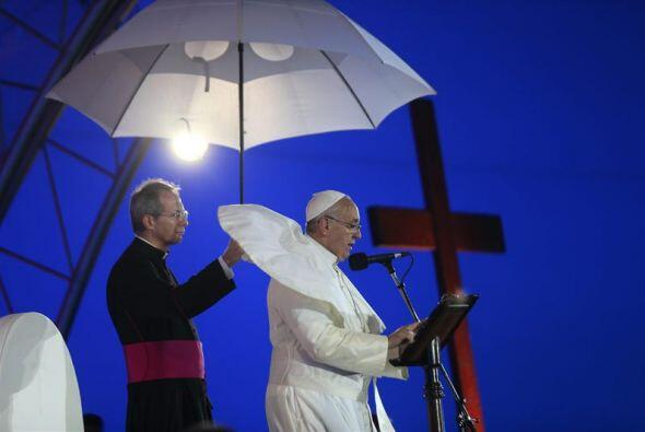 El papa Francisco, asistido por un obispo mientras el viento le vuela su...