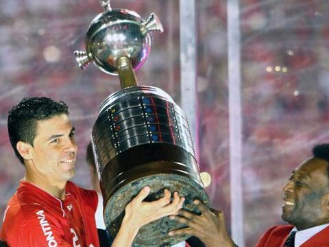 Pelé, que la ganó dos veces con el Santos, entregando la...