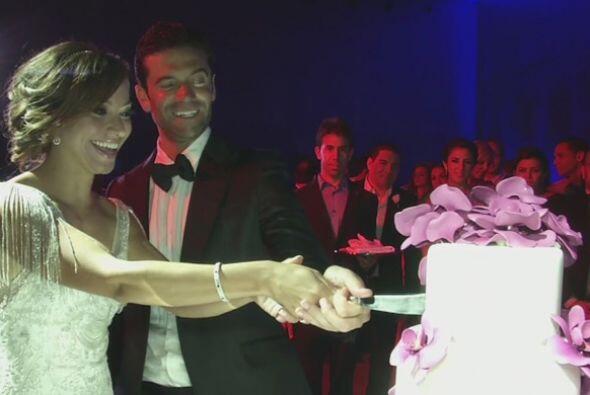 Los novios bromistas frente a su bello pastel de bodas.