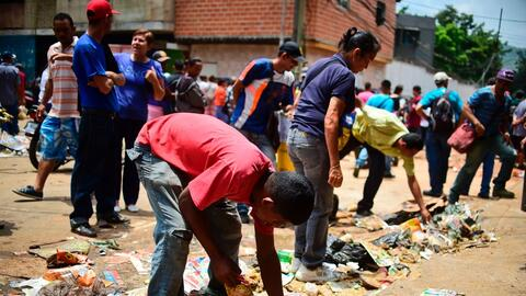 Residents of El Valle, in Caracas, search for food in the trash left aft...