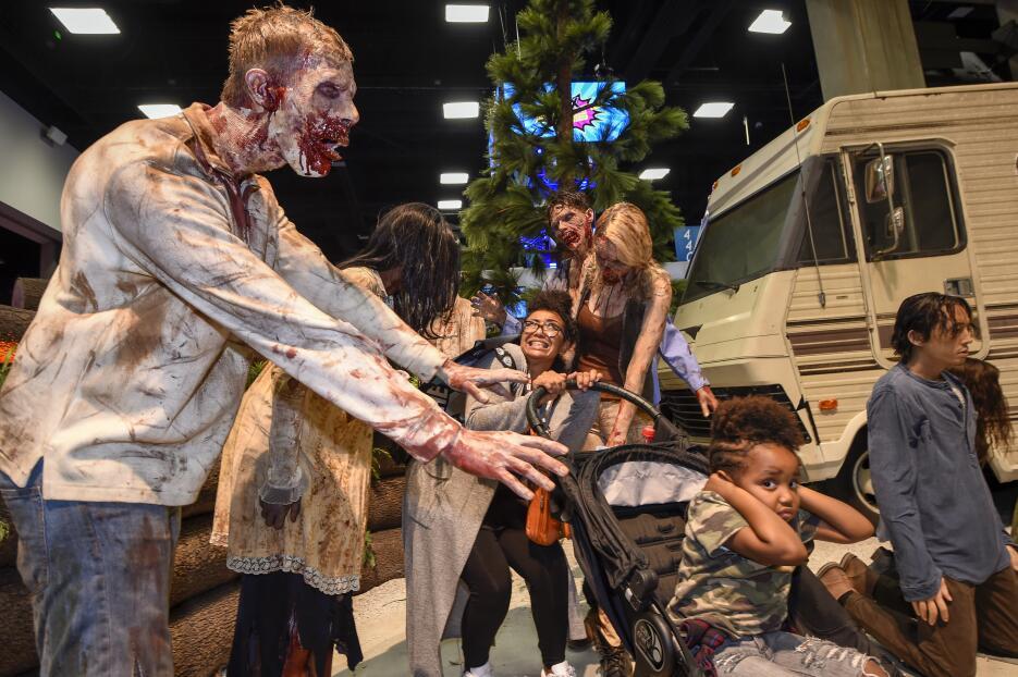 Fanáticos de 'The Walking Dead' posan con zombies de la serie.
