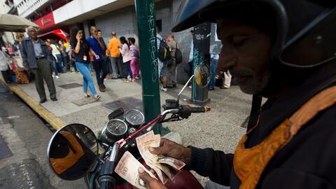 Un hombre cuenta sus billetes de 100 bolívares, antes de intentar...