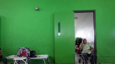Un hombre en silla de ruedas en una escuela que funciona como refugio en...