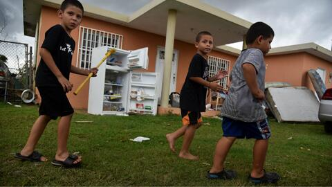 NIños frente a una residencia dañada por el huracán...