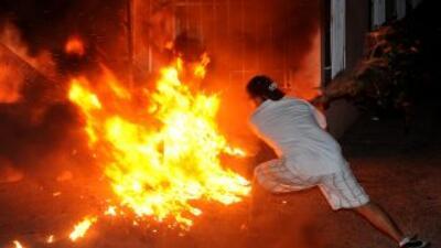 Manifestante enciende un fuego protestando por muerte de guatemalteco.