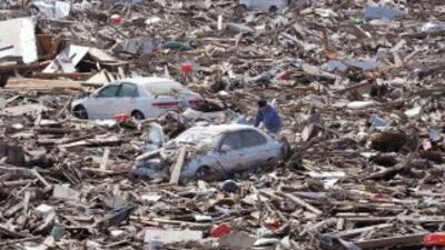 Una persona busca entre los escombros, en Sendai, una de las ciudades má...