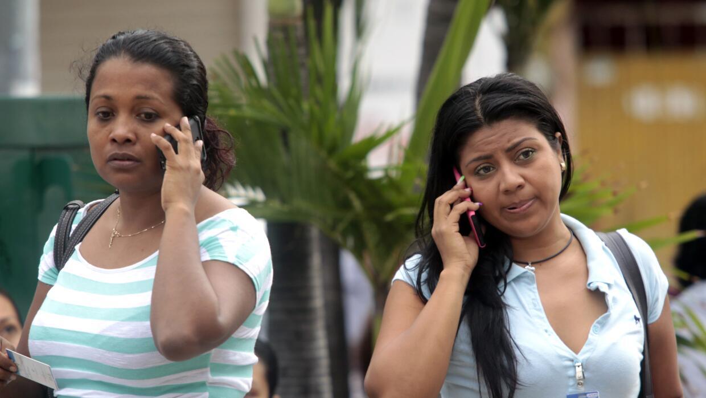 Dos mujeres mexicanas hablando a través de sus teléfonos móviles