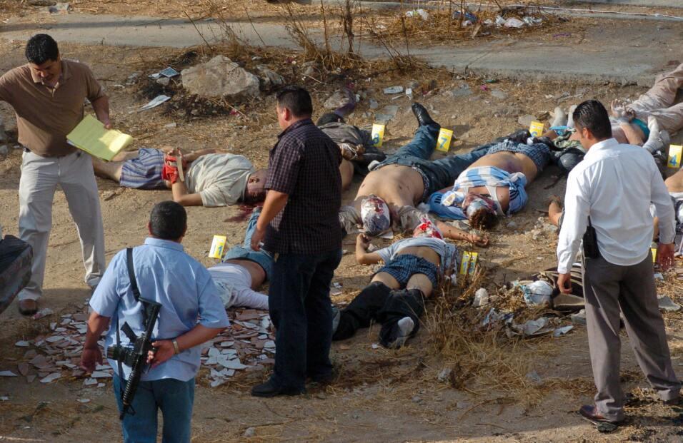 Detectives revisan la escena donde dejaron una docena de cuerpos.