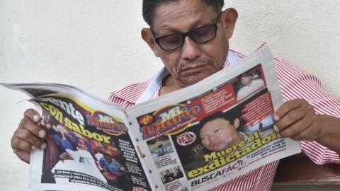 Un hombre lee un diario panameño que informa de la muerte de Manu...