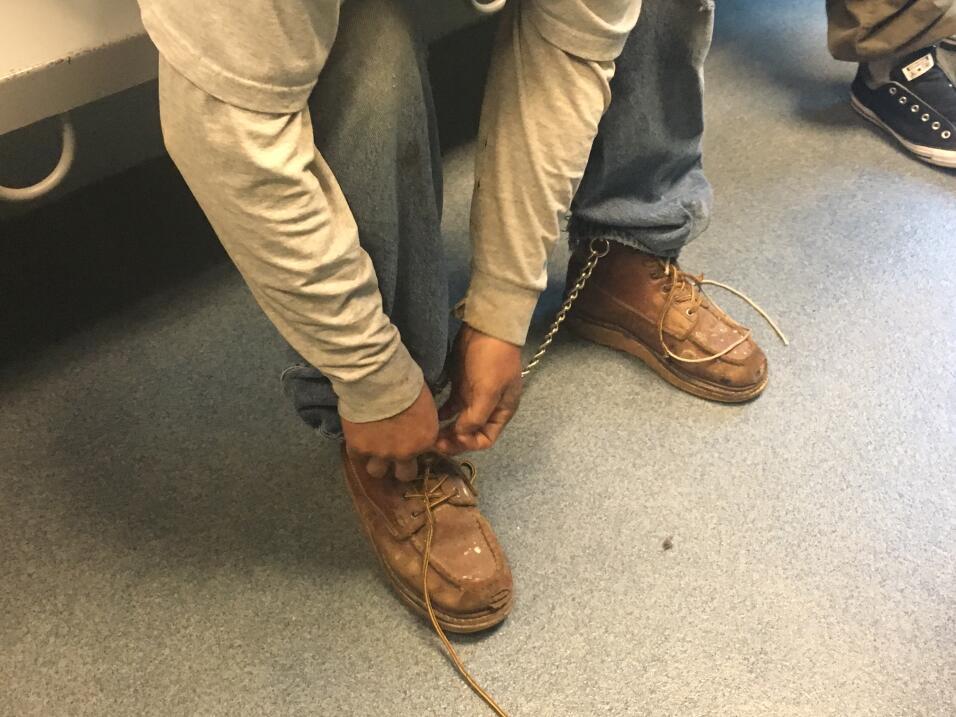 Carlos se quita las agujetas de sus botas antes de ser llevado a una celda.