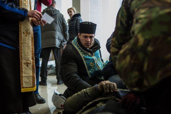 Un sacerdote asiste a uno de los manifestantes caídos en las prot...