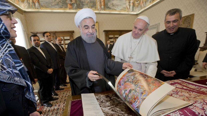 Hassan Rouhani junto al Papa Francisco y el libro que le dio como regalo.