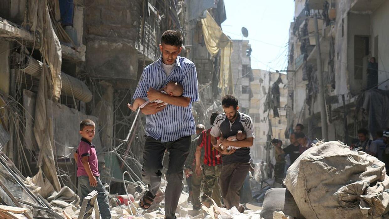Resultado de imagen para Un hombre carga un bebé tras un ataque en la norteña ciudad siria de Alepo.