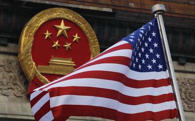 Una bandera estadounidense frente al símbolo patrio chino durante...