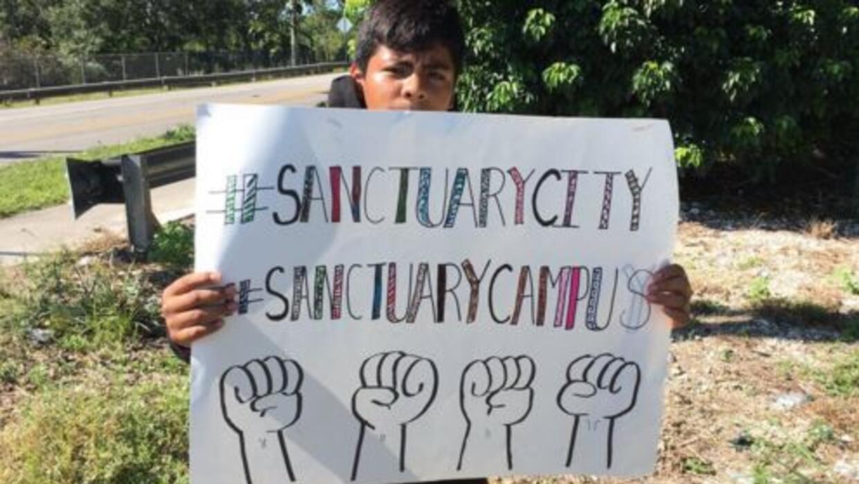 Un joven en Miami con un cartel a favor de las ciudades y los campus san...