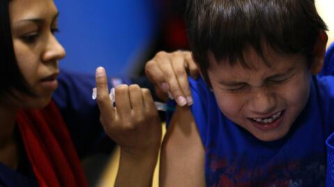 Un niño recibe una vacuna de la gripe.