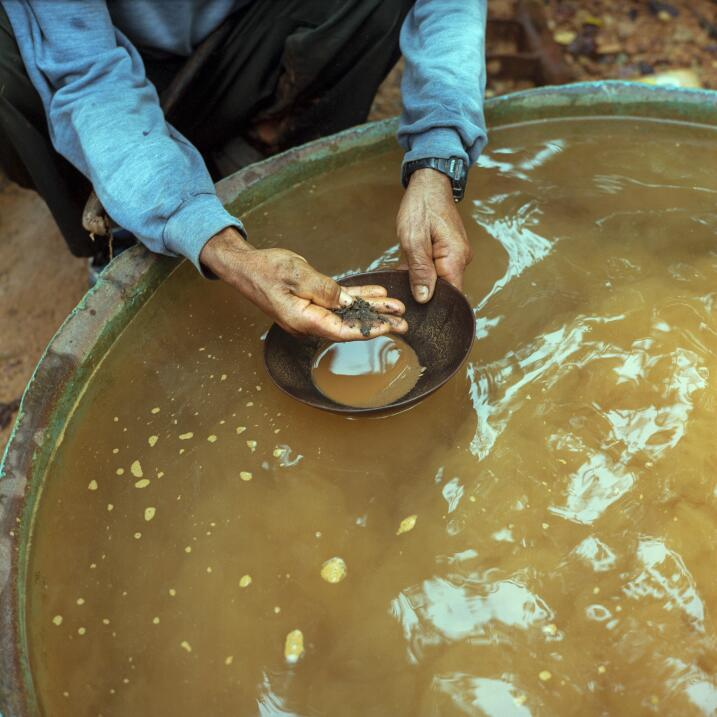 Jose Perriera Cunha, known as Perilito, shows some gold flakes in a pan....