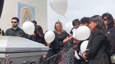 La niña mayor de los García llora junto a sus hermanos durante el funera...