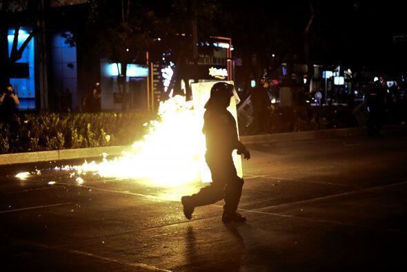 Uno de los policías evade una bomba molotov.