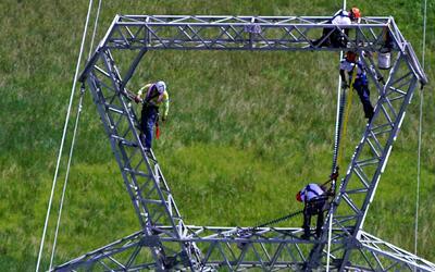 Celadores de línea de Whitefish trabajan en una torre eléc...