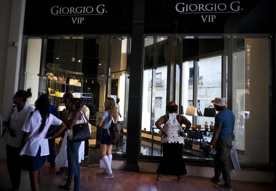 Un grupo de personas mira los escaparates de las tiendas de lujo en el h...