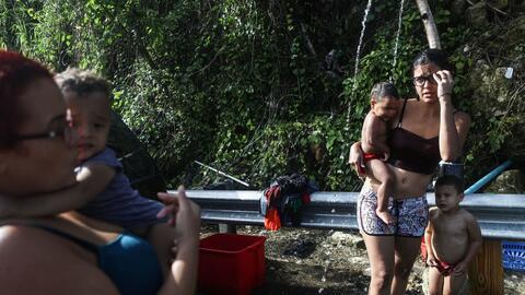 Anais Rivera, a la derecha, tiene la asistencia de una amiga para lavar...