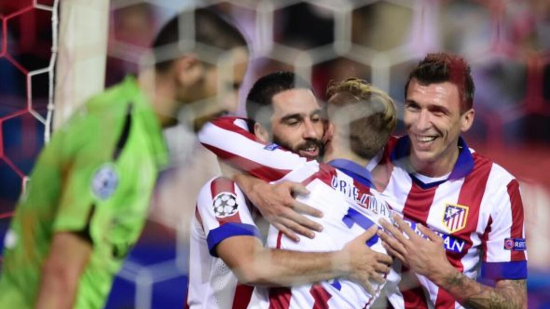 Turan es felicitado por Griezmann y Mandzukic, luego de hacer el gol con...