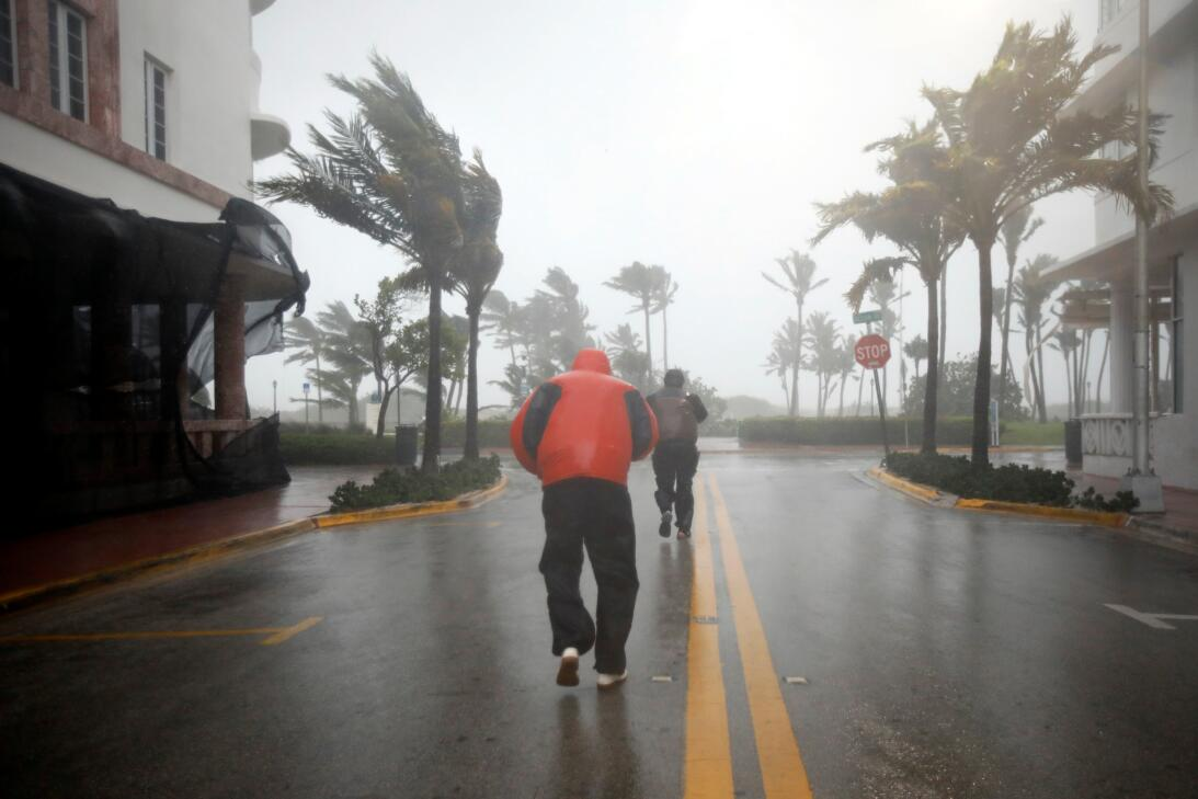People walk along a street in South Beach as Hurricane Irma arrives at s...