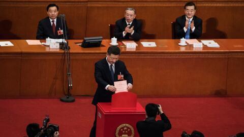 El presidente Xi Jinping coloca su boleta durante una votación so...
