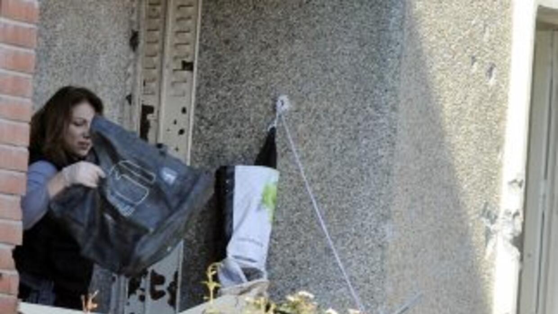 Una mujer policía recopila evidencias en el balcón del departamento dond...