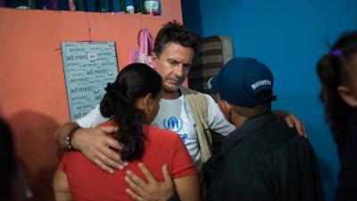Osvaldo Laport abraza a dos refugiados.