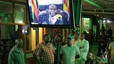 Zimbabuenses viendo en un local el anuncio televisado de Mugabe, quien s...