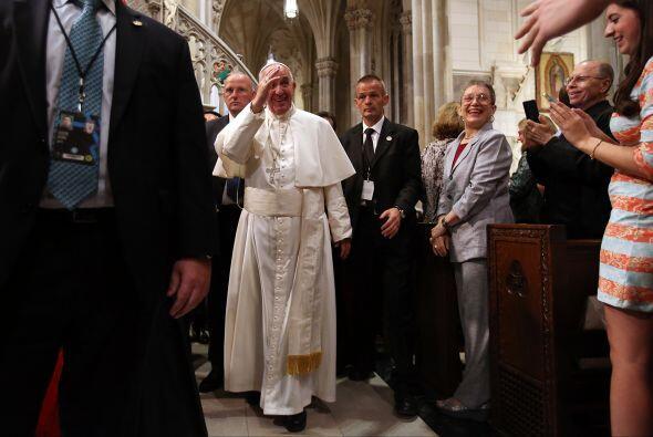 Personas esperando por el paso del Papa, quien les saluda.