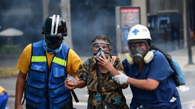 Personal paramédico atiende a una señora afectada por los gases lacrimóg...