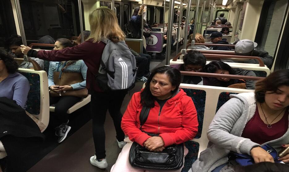 Alejandra Morán, de suéter rojo, viaja hacia la estación Universal City...