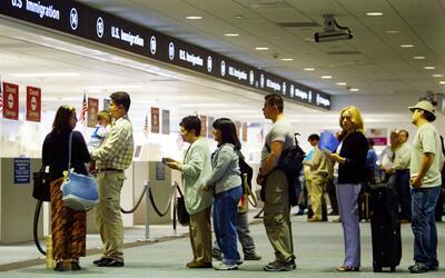 Personas esperan en fila para entrar a Estados Unidos en el aeropuerto d...
