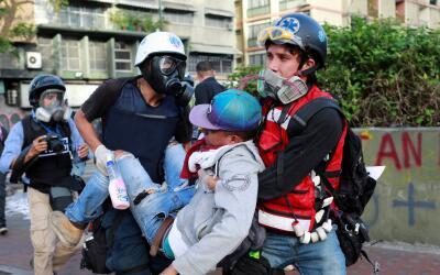 Socorristas llevan cargado a un joven que resultó herido en una p...