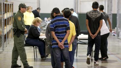 Un grupo de niños migrantes es procesado en un centro de detención de la...